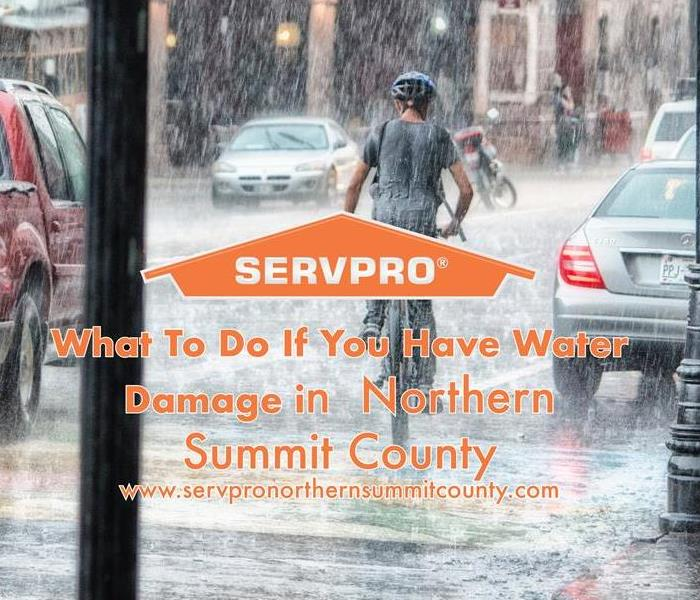 Orange SERVPRO house logo on a rainy image with cars and person riding bike.