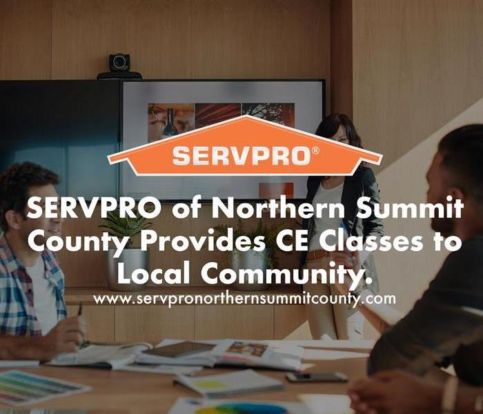Orange SERVPRO  house logo on image with presentation classroom.